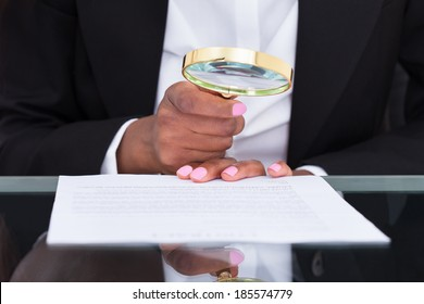 Midsection of businesswoman using magnifying glass to read document at desk in office