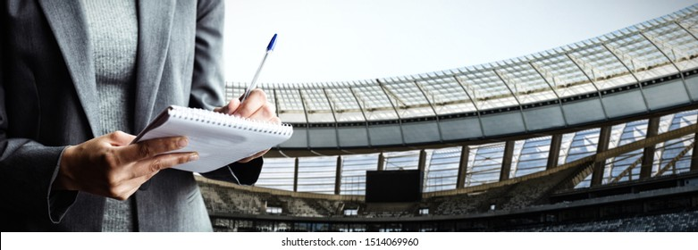 Midsection of businesswoman writing on note pad against rugby goal post on a sunny day in the stadium