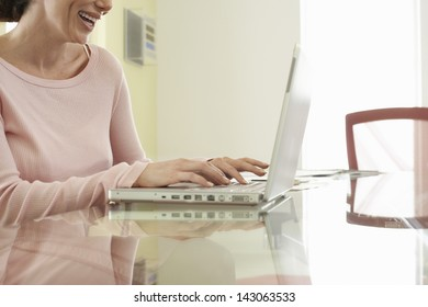 Midsection of cheerful businesswoman using laptop at office table