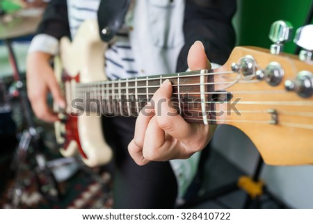 Midsection closeup of woman playing guitar in recording studio