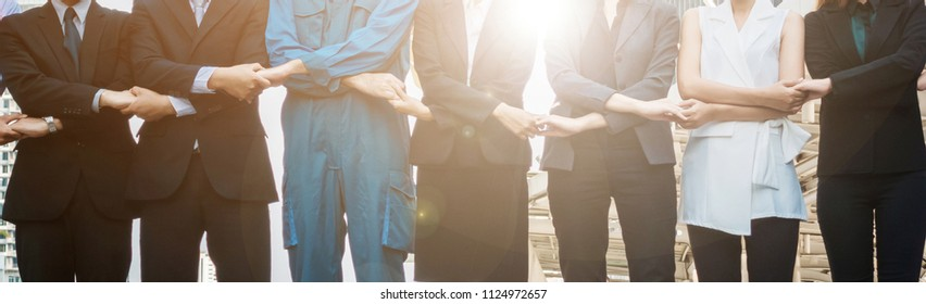 Midsection Of Colleagues With Holding Hands Standing In City