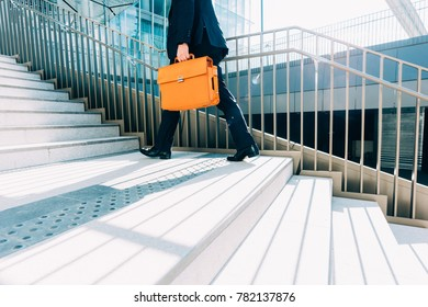 midsection contemporary business man walking upstairs in the city backlight, holding overnight bag - business, work concept