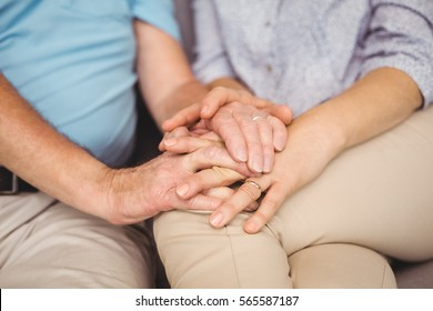 Midsection of couple holding hands while comferting eachother