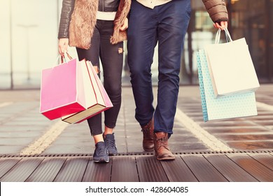 Photo of Midsection of couple with shopping bags in city