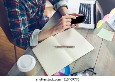 Midsection of creative editor using cellphone and laptop at office