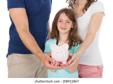 Midsection of family holding piggy bank together