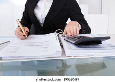 Midsection of female accountant calculating tax at desk in office
