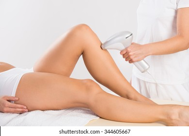 Midsection of female beautician using laser machine on customer's leg at salon