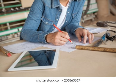 Midsection of female carpenter drawing on blueprint at table in workshop