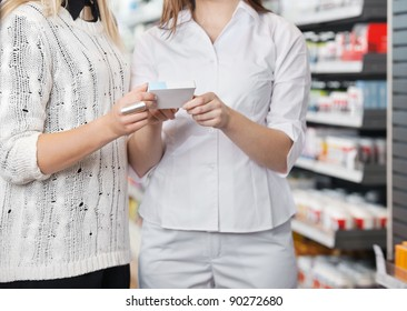 Mid-section of female pharmacist advising customer how to take medicine