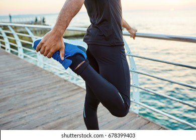 Midsection of fit dark-skinned sportsman warming up his muscles, stretching his legs, doing standing quadricep front thigh stretch before running workout in the morning, facing sea.