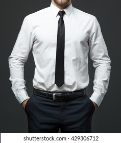 Midsection of fit young businessman standing in formal white shirt, black tie and pants.