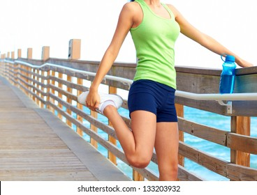 Midsection of healthy young woman stretching her leg during exercise on bridge. Horizontal shot. Pretty mixed racial fitness woman stretching on the boardwalk at Dania Beach in South Florida.