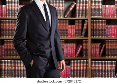 Midsection of lawyer with hand in pocket against books in shelves