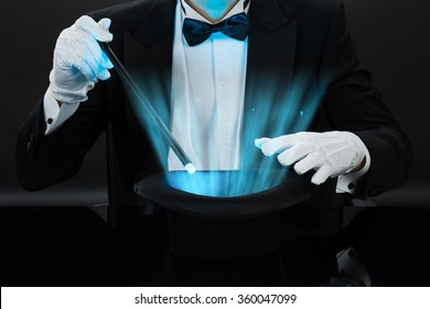 Midsection of magician holding magic wand over illuminated hat against black background