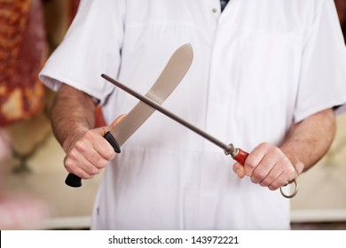 Midsection of male butcher sharpening knife in shop