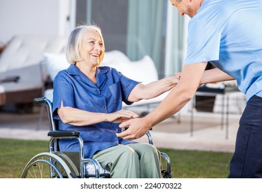 Midsection of male caretaker helping senior woman to get up from wheelchair at nursing home lawn