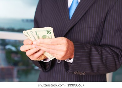 Midsection of male corporate executive in a business suit counting money. Horizontal shot.
