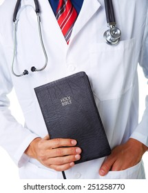 Midsection of male doctor holding Bible against white background