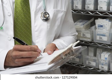 Midsection of male doctor writing a prescription while standing by medical supplies on rack