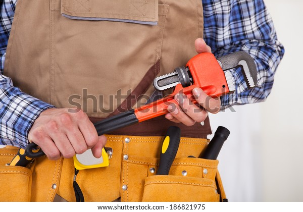 Midsection of male repairman with tool belt holding pipe wrench