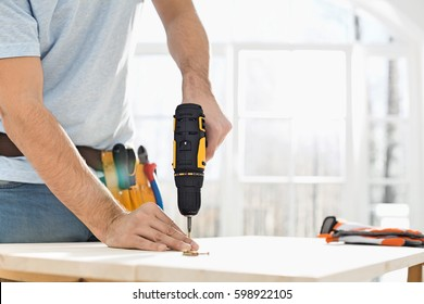 Midsection of man drilling nail on table