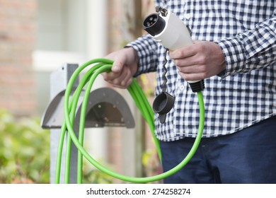Midsection of man holding electric car charging plug with green cord