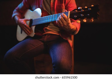 Mid-section of man playing guitar in pub