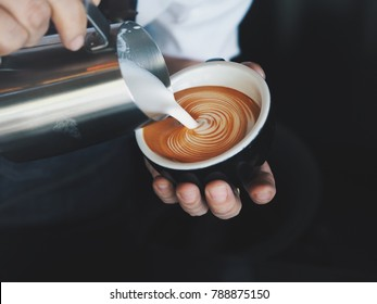 Midsection of man pouring milk in coffee cup.