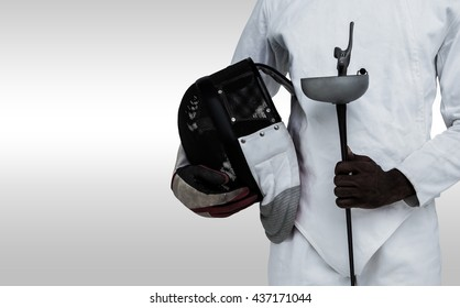 Mid-section of man standing with fencing mask and sword against grey background