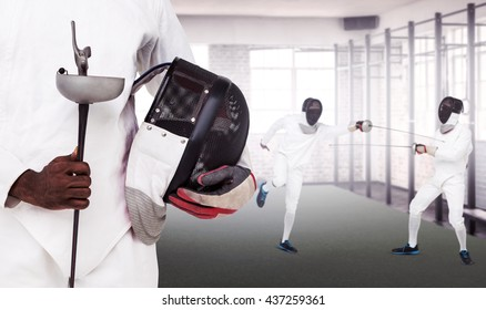 Mid-section of man standing with fencing mask and sword against gym