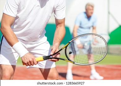 Midsection of man standing with tennis racket against friend playing doubles match on court