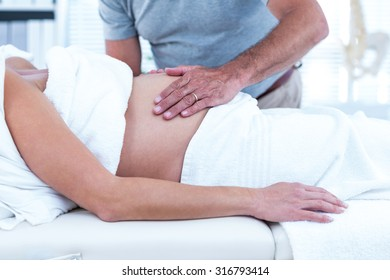 Midsection of masseur giving massage to pregnant woman sleeping on bed in spa