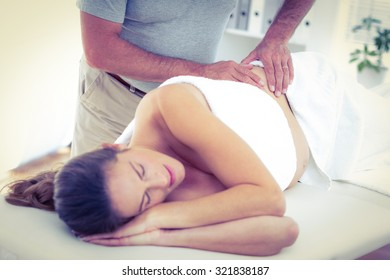Midsection of masseur giving massage to woman sleeping on bed in spa