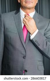 Midsection of mature businessman adjusting necktie