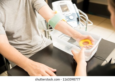 Midsection of mature man receiving electrotherapy from physiotherapist in hospital