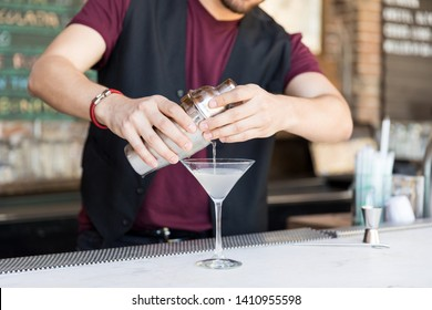 Midsection of mixologist pouring cocktail from shaker in martini glass at restaurant