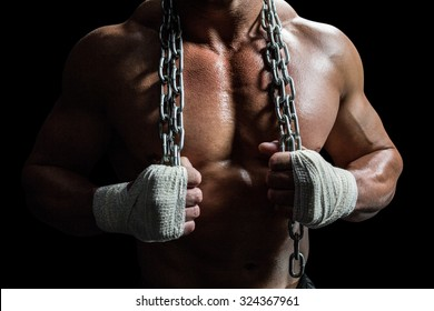 Midsection of muscular man holding chain against black background