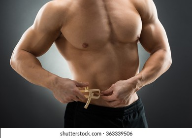 Midsection of muscular man measuring fats with caliper against black background
