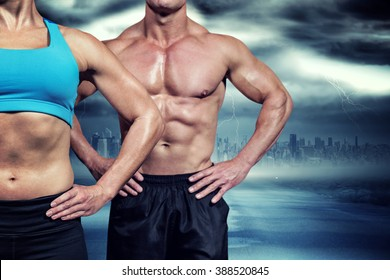 Midsection of muscular woman and man standing with hands on hip against stormy sky with tornado over road