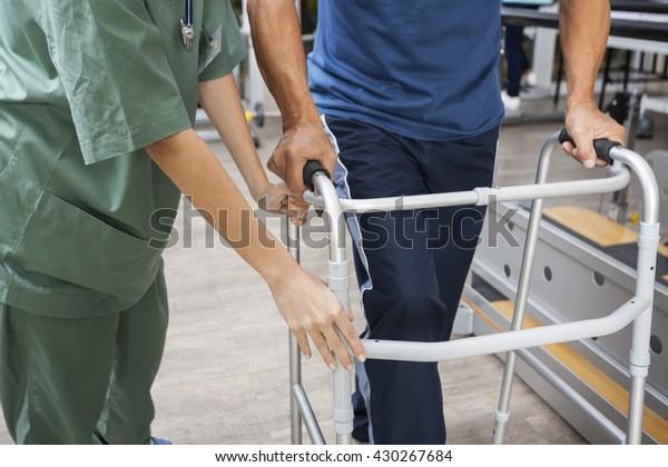 Midsection Of Nurse Assisting Senior Man To Walk Using Walker