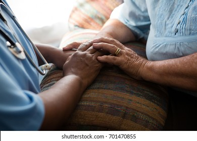 Midsection of nurse and patient relaxing at sofa in nursing home