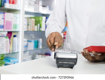 Midsection Of Pharmacist Swiping Credit Card While Holding Produ