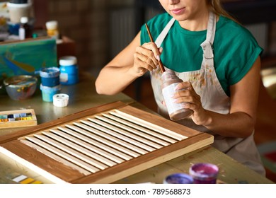 Mid-section portrait of young female artist enjoying work in art studio painting shutters with bronze paint, making DIY interior decoration