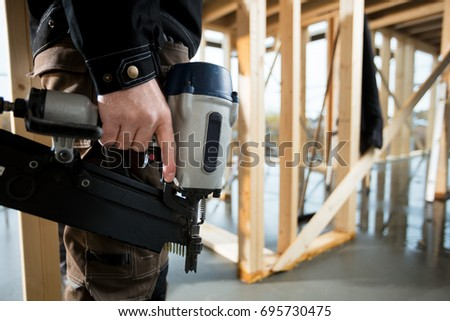 Midsection Of Professional Carpenter Holding Drill Machine