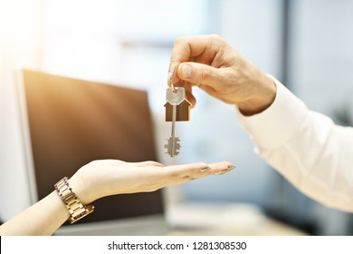Midsection of real estate agent and buyer hands with keys