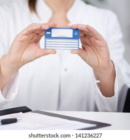 Midsection of receptionist showing medical card at counter in hospital