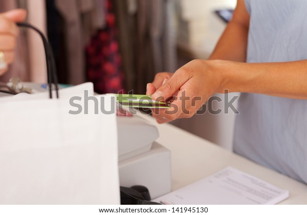 Midsection of saleswoman holding credit card from customer while using cash desk at boutique counter
