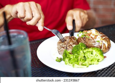 Midsection of senior man eating strip steak served with loaded baked potato and broccoli at restaurant table
