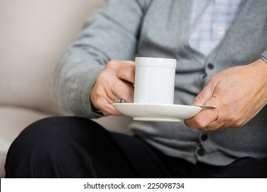 Midsection of senior man holding coffee cup while sitting on couch at nursing home